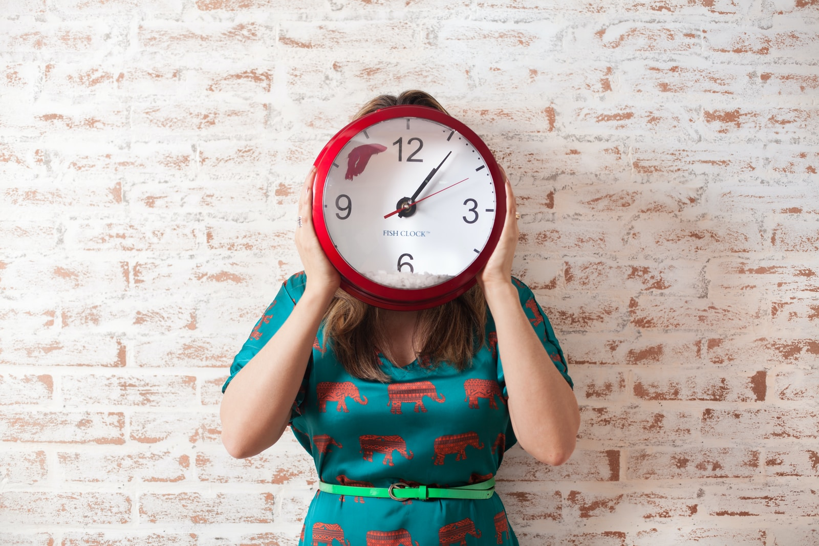 woman covering face using wall clock